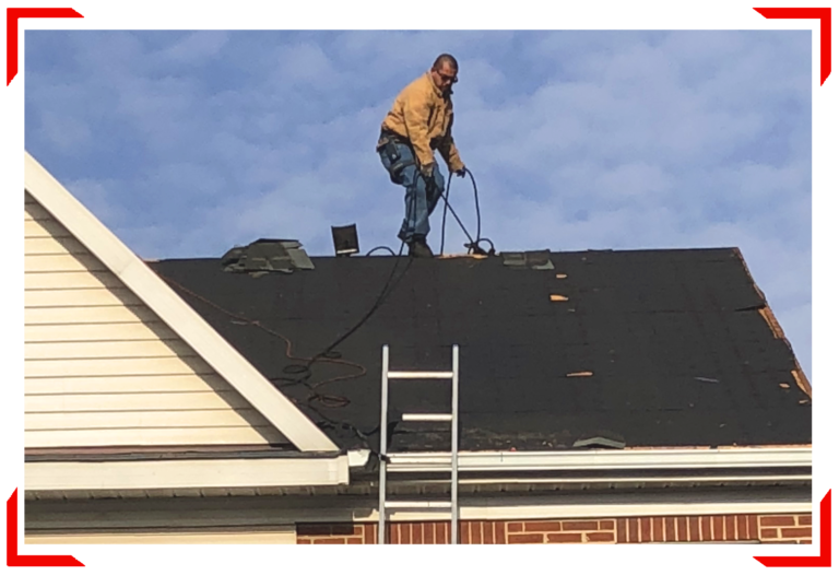 Man on top of roof repairing with cords and ladder
